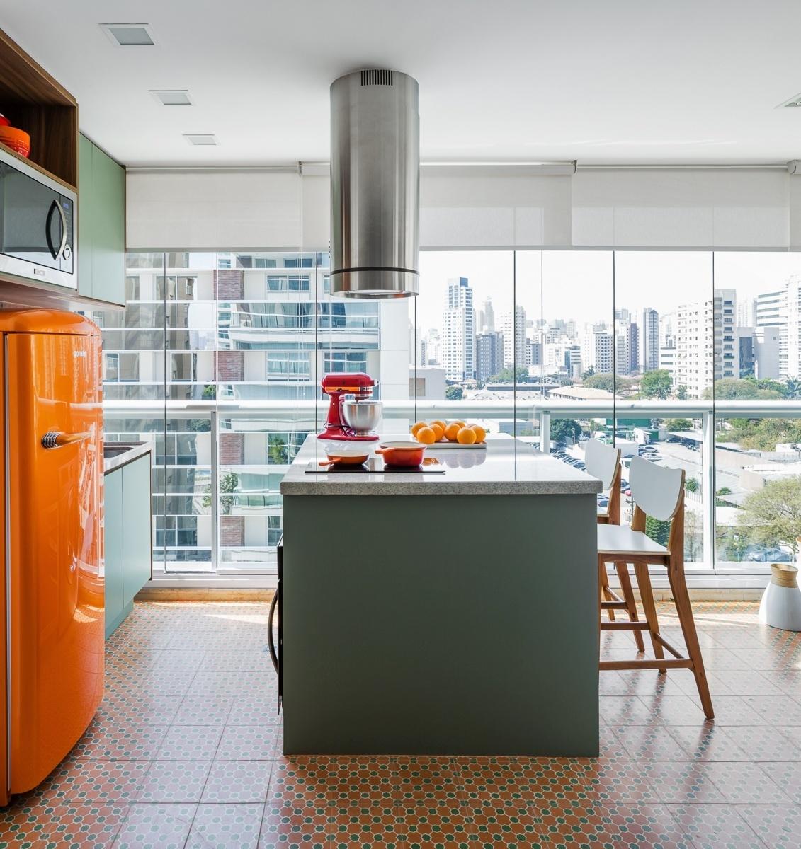 A varanda do apê Affinity foi transformada em uma gostosa cozinha com uma ilha que abriga cooktop e forno e serve como mesa. Destaque para a geladeira retrô, da Gorenje, e o piso colorido formado pelos ladrilhos hidráulicos da Ornatos. O projeto de reforma é da arquiteta Marcela Madureira