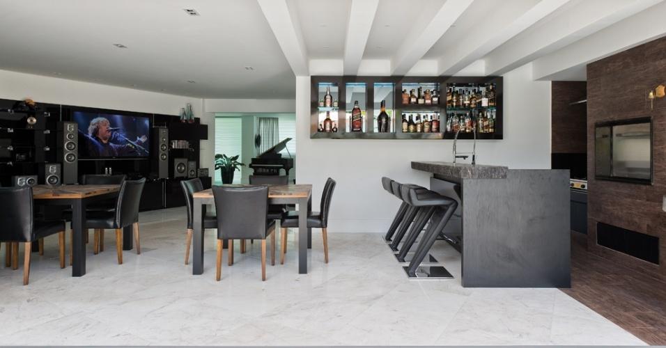 A área da churrasqueira da casa Alphaville integra-se à piscina e à sala de jantar. O piso em mármore piguês dá continuidade ao empregado na área social interna, dominada pelo living. No espaço, o bar tem acabamento de granito com bordas apicoadas. O interiores são uma criação da arquiteta Carla Kiss