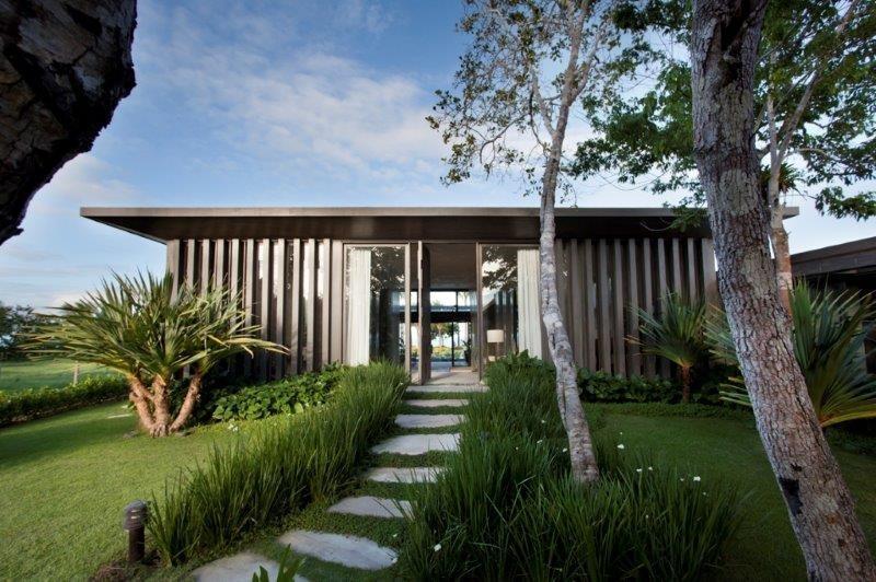 O acesso à residência em Trancoso (BA) se dá pelo caminho desenhado com placas de arenito em meio ao verde do jardim. As colunas em madeira com fechamento de vidro formam a fachada da casa de praia desenvolvida pela arquiteta Debora Aguiar