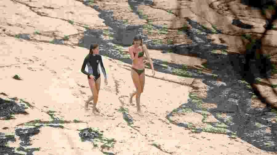 Mulheres caminham em praia coberta por cinzas em Mallacoota, Austrália  - Tracey Nearmy/Reuters