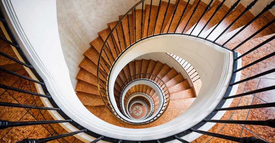O guarda-corpo da escadaria é feito em ferro e foi instalado sobre uma base branca com detalhes de gesso. As pedras que formam os degraus têm continuidade nos patamares e dão forma à estrela na base térrea da escada