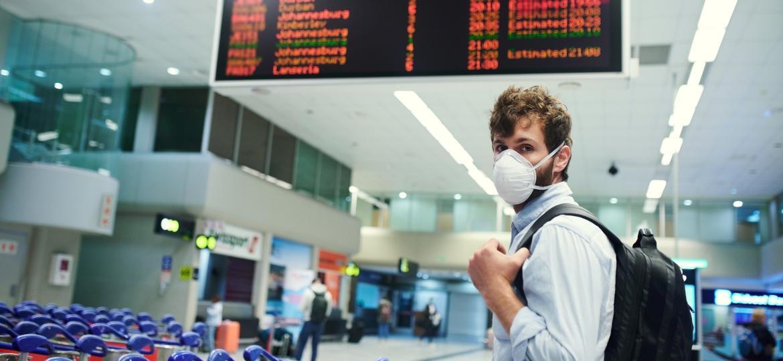 Homem usa máscara em aeroporto - Getty Images