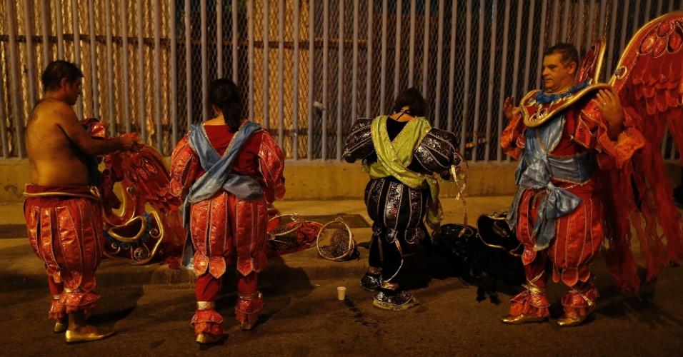 8.fev.2016 - Integrantes tiram as fantasias, após desfilarem na 1ª noite do Grupo Especial na Sapucaí