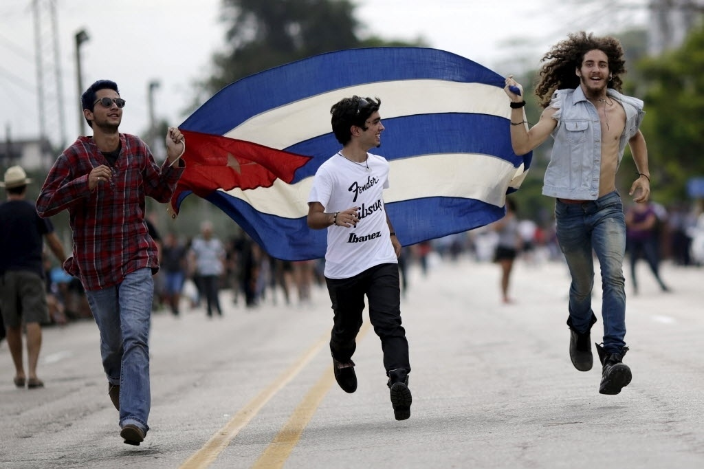 25.mar.2016 - Fãs correm com a bandeira de Cuba à espera do show gratuito dos Rolling Stones na Cidade Esportiva em Havana