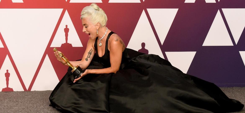 """Lady Gaga admira o Oscar que ganhou de melhor canção por """"Shallow"""", de """"Nasce Uma Estrela"""" - Frazer Harrison/Getty Images"""