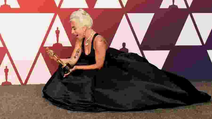 Lady Gaga admira o Oscar que ganhou de melhor canção por Shallow, de Nasce Uma Estrela - Frazer Harrison/Getty Images