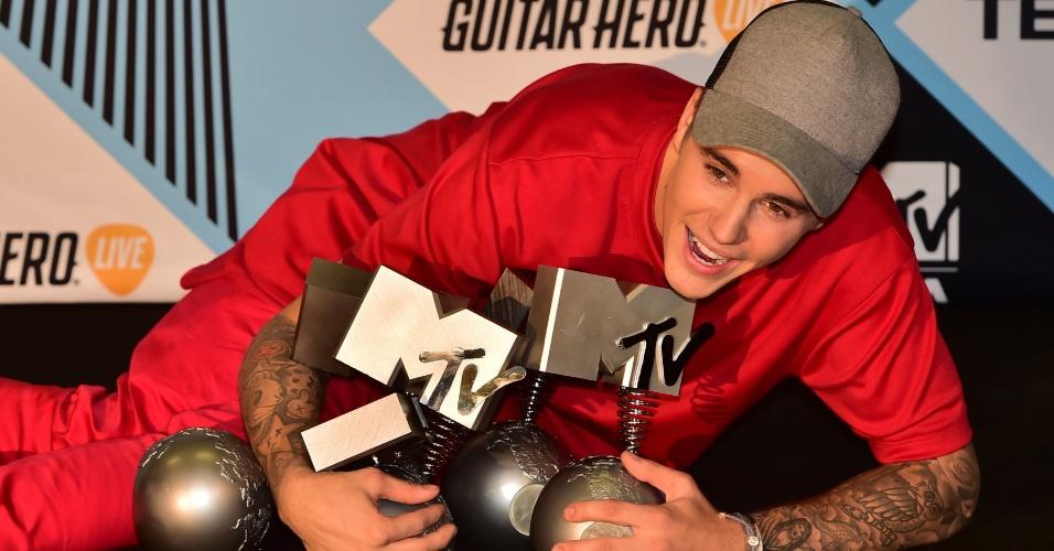 Cantor canadense Justin Bieber posa com todos os troféus conquistados no EMA 2015