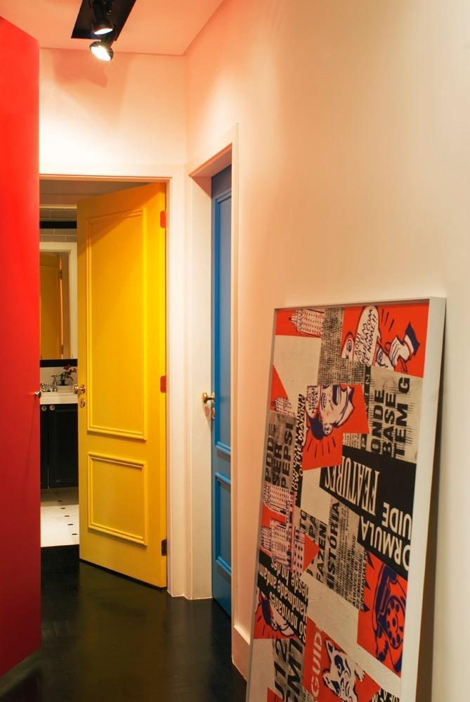 O corredor para área íntima recria o estilo cinquentista ?por art?, expresso nas cores das portas da suíte (amarelo) e do quarto de hóspedes (azul), em combinação com poster encostado na parede. O Apartamento Higienópolis, em São Paulo, foi projetado pela D2N Arquitetura e Interiores