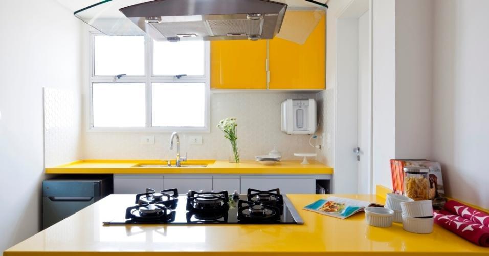 A cozinha era pequena, por isso um quarto de empregada foi demolido e incorporado ao espaço. Na ilha de cocção, o 'cooktop' (Electrolux) fica apoiado sobre bancada (Vulcana Stone - Yellow Regolare) de superfície super sólida composta de quartzo e plástico, o mesmo usado na pia (ao fundo). A reforma é assinada pelo escritório Iná Arquitetura