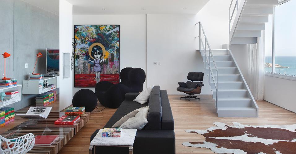 O escritório InTown seguiu uma linguagem moderna no projeto de interiores da cobertura no Rio de Janeiro (RJ). Na sala de estar, por exemplo, há peças contemporâneas como a poltrona preta Up5_6 (1969), com pufe, uma criação do italiano Gaetano Pesce
