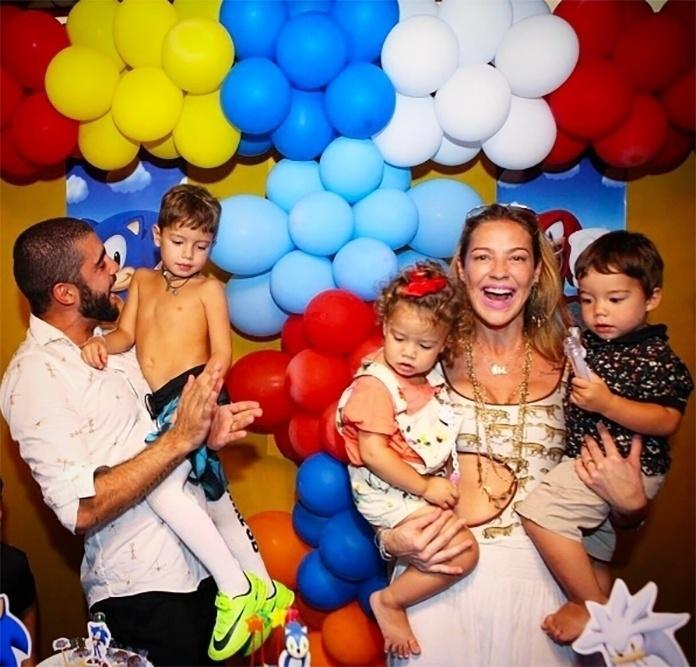 Luana Piovani compartilhou uma foto da festa de aniversário de 5 anos do seu filho mais velho, Dom. Ao lado do marido, Pedro Scooby, a atriz aparece segurando os gêmeos, Liz e Ben.