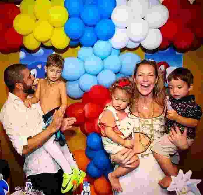 Luana Piovani compartilhou uma foto da festa de aniversário de 5 anos do seu filho mais velho, Dom. Ao lado do marido, Pedro Scooby, a atriz aparece segurando os gêmeos, Liz e Ben.  - Reprodução/Instagram