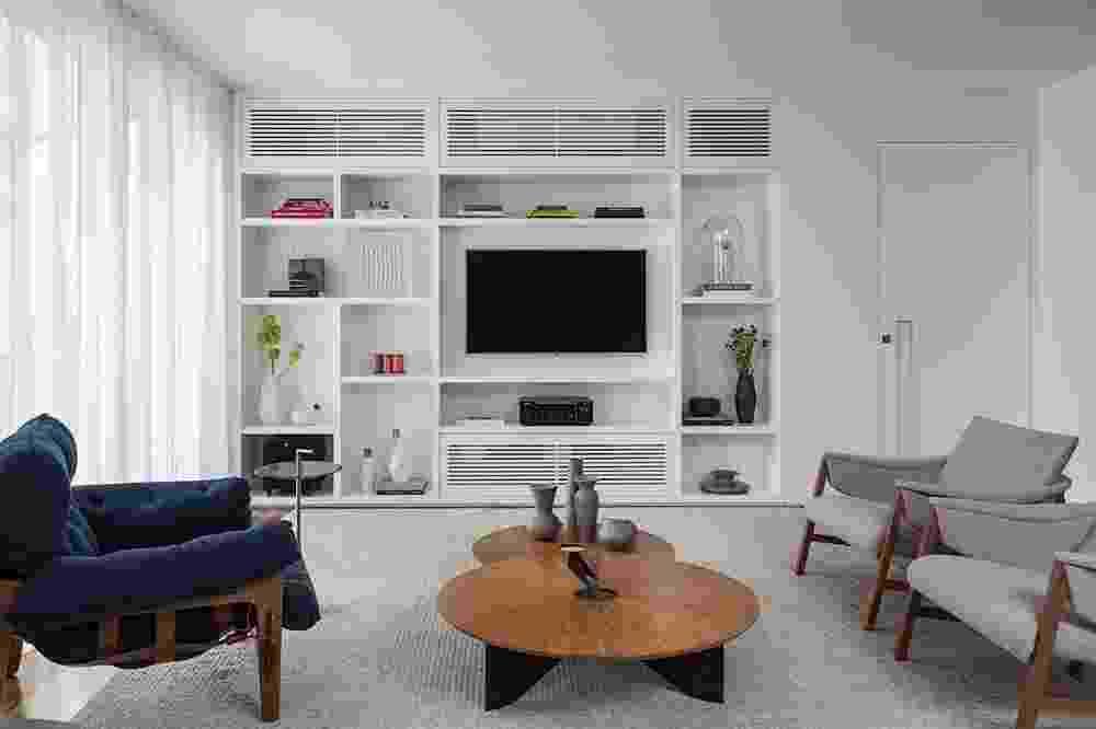 Se a ideia é fazer com que sua sala de estar pareça maior, que tal abrir mão do sofá? No lugar da peça, invista em bancos acolchoados, pufes, almofadas sobre o tapete e até futons. Poltronas, por serem compactas, também são bem-vindas e foram as apostas neste projeto do escritório Sala 2 Arquitetura e Design - Evelyn Muller / Divulgação