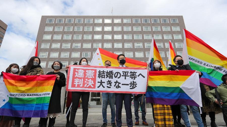 """17.mar.2021 - Manifestantes seguram bandeira de """"decisão inconstitucional"""" após decisão de um tribunal do Japão de que é inconstitucional não reconhecer o casamento entre pessoas do mesmo sexo - STR/JIJI Press/AFP"""