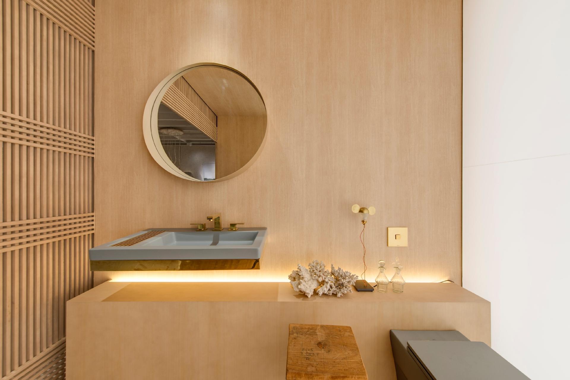 A estrutura divisória (à esq.) do banheiro do apê Shoji 04, assinado pelo escritório Yamagata, é treliçada e feita em madeira clara. O espelho circular cria um contraponto com o lavatório fino de encaixe, decorado com metais dourados. Sobre a bancada cimentícia, objetos de decoração, como a luminária 'The I Ricchi Poveri - Toto', desenhada por Ingo Maurer