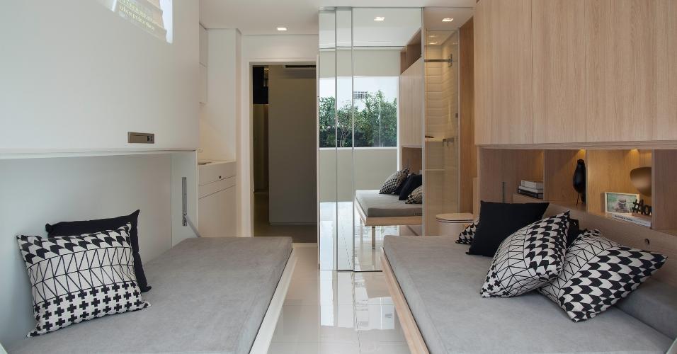 O apê parece apertado, mas conta com a dupla de sofás-cama. Quando o ambiente é usado como sala, a iluminação com spots embutidos no teto e nos nichos dos armários fica mais forte.
