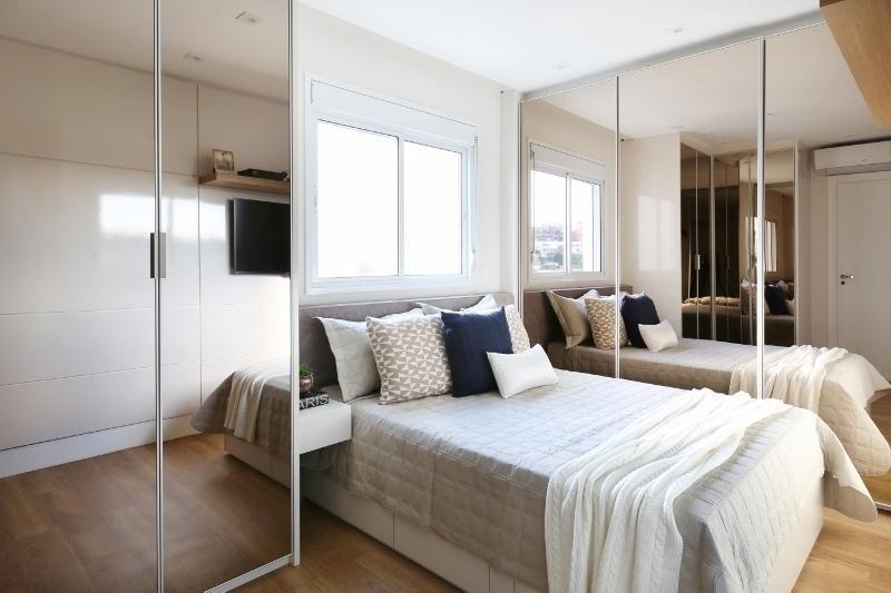 A grande quantidade de armários no quarto estreito foi atenuada pelas portas espelhadas, usadas para trazer amplitude e melhorar a iluminação
