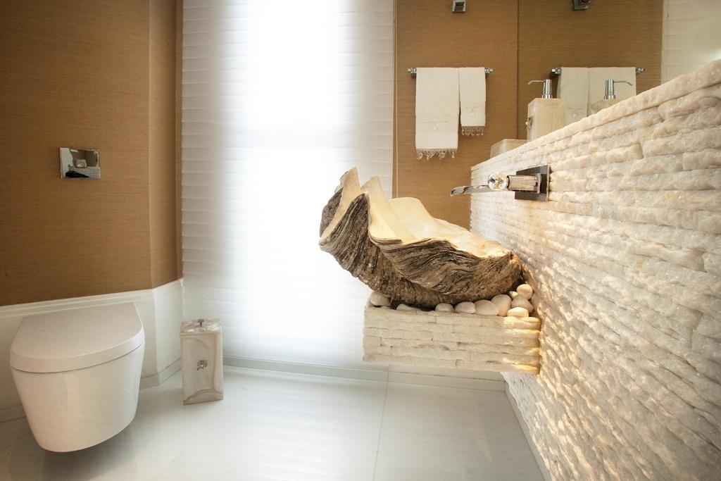Parte das paredes do lavabo é revestida com palha sintética Revolution, da By Kami, fácil de limpar. A cuba foi feita com uma concha com 400 anos, vinda das Filipinas, que já pertencia à família proprietária da casa Acapulco. O apoio foi feito com filetes de mármore Thassos.