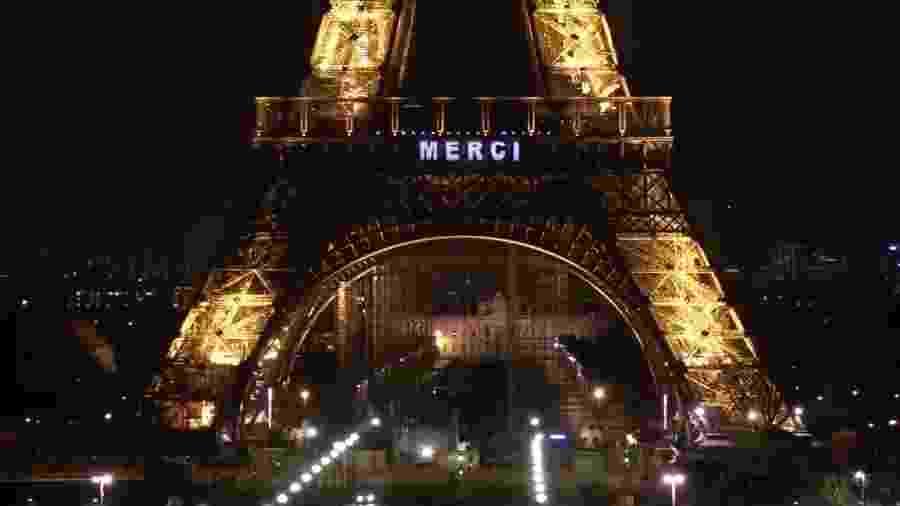 """Torre Eiffel foi iluminada com mensagens de agradecimento, como """"Merci"""" (""""Obrigado"""", em francês), em homenagem aos profissionais da saúde  - Reprodução/Twitter"""