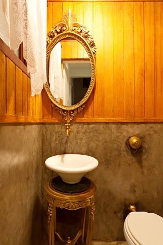 Mix incomum - As designers de interiores Márcia e Melina Mundim apostaram em uma combinação pouco convencional de materiais para compor este lavabo: nas paredes há ripado de madeira e cimento queimado. No suporte para a cuba e em parte dos acessórios, o metal dourado com adornos dá personalidade ao ambiente