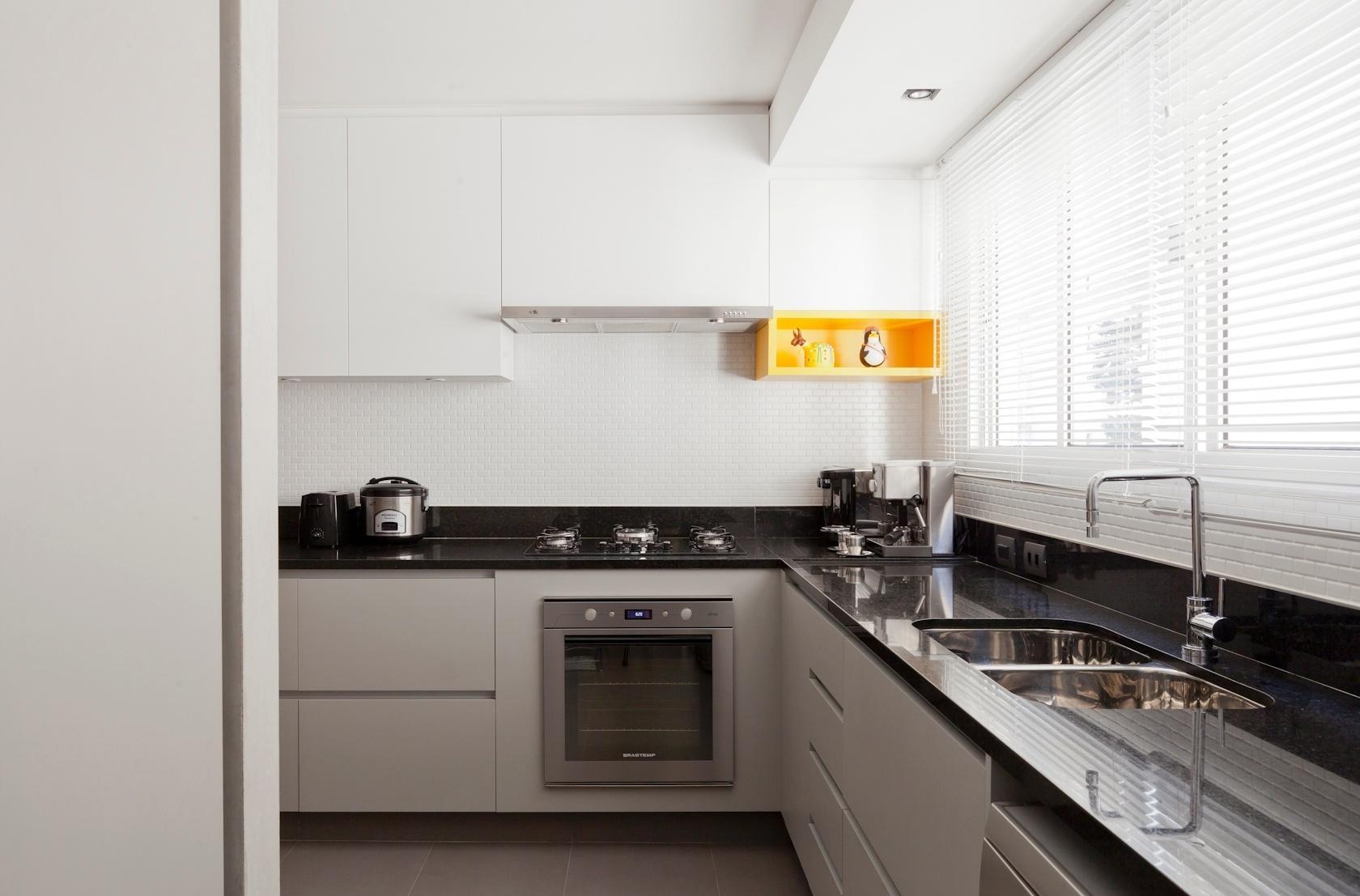 Parte da cozinha do apartamento de 160 m2, no Paraíso, zona sul de São Paulo. A bancada em massa sintética de vidro preta guarda armários revestidos de laminado melamínico cinza claro em composição com os suspensos brancos. Na parede, o arquiteto Renato Dalla Marta, autor do projeto de reforma, definiu pastilhas cerâmicas brancas