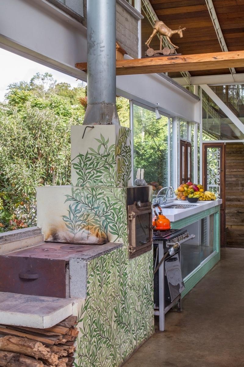 O fogão à lenha teve suas paredes pintadas pela artista plástica Katharina Welper. Segundo o arquiteto Rodrigo Simão, autor do projeto da casa Samambaia, quando o sistema atinge 300° C, uma pizza pode ser assada em apenas um minuto. Nos dias frios, o fogão funciona como aquecedor