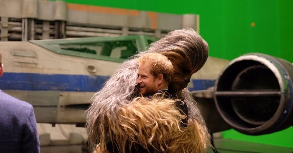 19.abr.2016 - Príncipe Harry ganha abraço de Chewbacca durante visita aos estúdios de