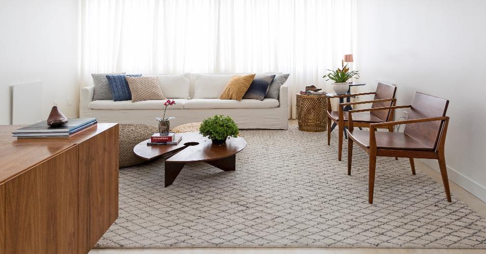 Já que a sala é totalmente integrada aos demais ambientes do apartamento, o escritório Tria Arquitetura preferiu escolher um tapete neutro, com listras azuis discretas, para não sobressair demais e chamar mais atenção do que o entorno