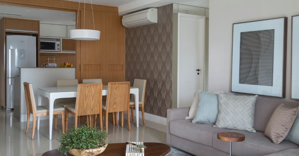 Acabamentos na cor branca e em madeira (freijó) definem a cozinha deste apartamento em São Paulo (SP), projetado por Ana Yoshida. Quando a porta de correr (Marcenaria Edlucas) está aberta, o cômodo se integra ao living, permitindo a interação dos moradores com as visitas