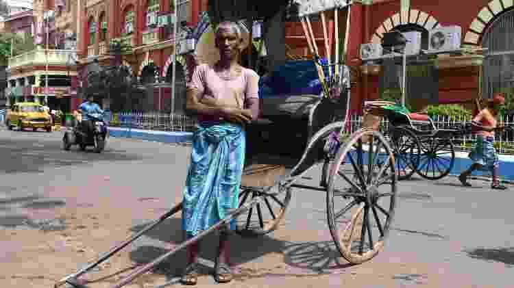 O indiano Mohammad Ashgar, 65, um condutor de riquixá, meio de transporte que só existe ainda em Calcutá. A associação local estima que haja 3 mil condutores na cidade - Dibyangshu Sarkar/AFP Photo - Dibyangshu Sarkar/AFP Photo