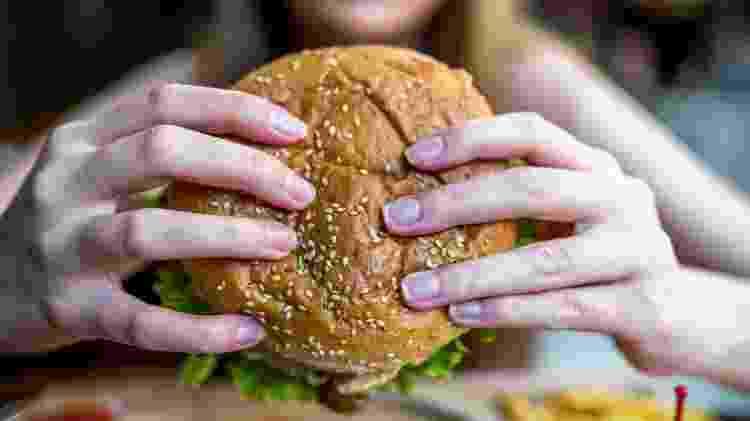 fast food, pessoa comendo hamburguer - iStock - iStock