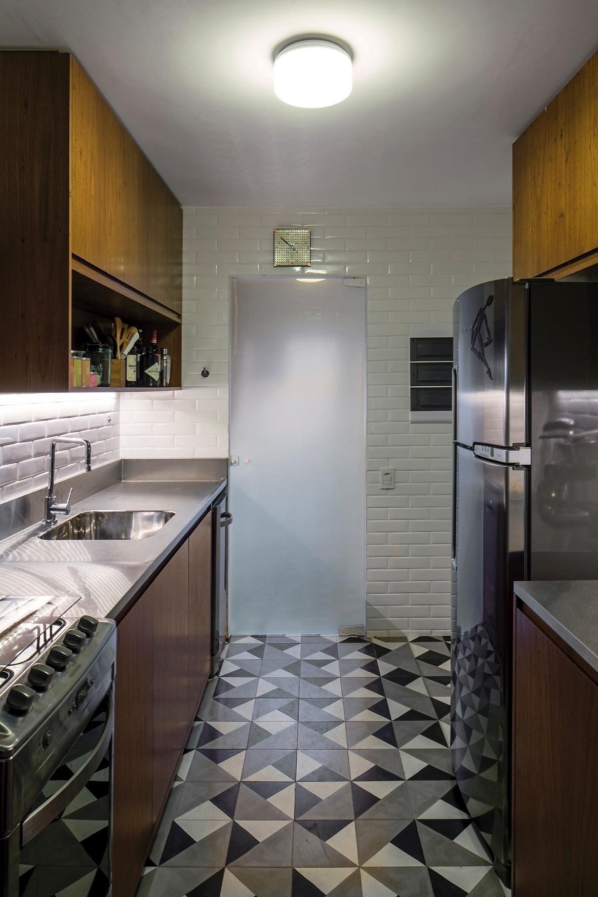 Na cozinha, o piso de ladrilhos hidráulicos (Casa Franceza) foi combinado às bancadas em aço inox (Mekal) e à marcenaria em madeira natural, que aquece o ambiente. As cores que dominam o espaço variam do branco ao preto. A reforma do Apartamento FT é assinada pelos arquitetos do escritório Pascali Semerdjian, em São Paulo