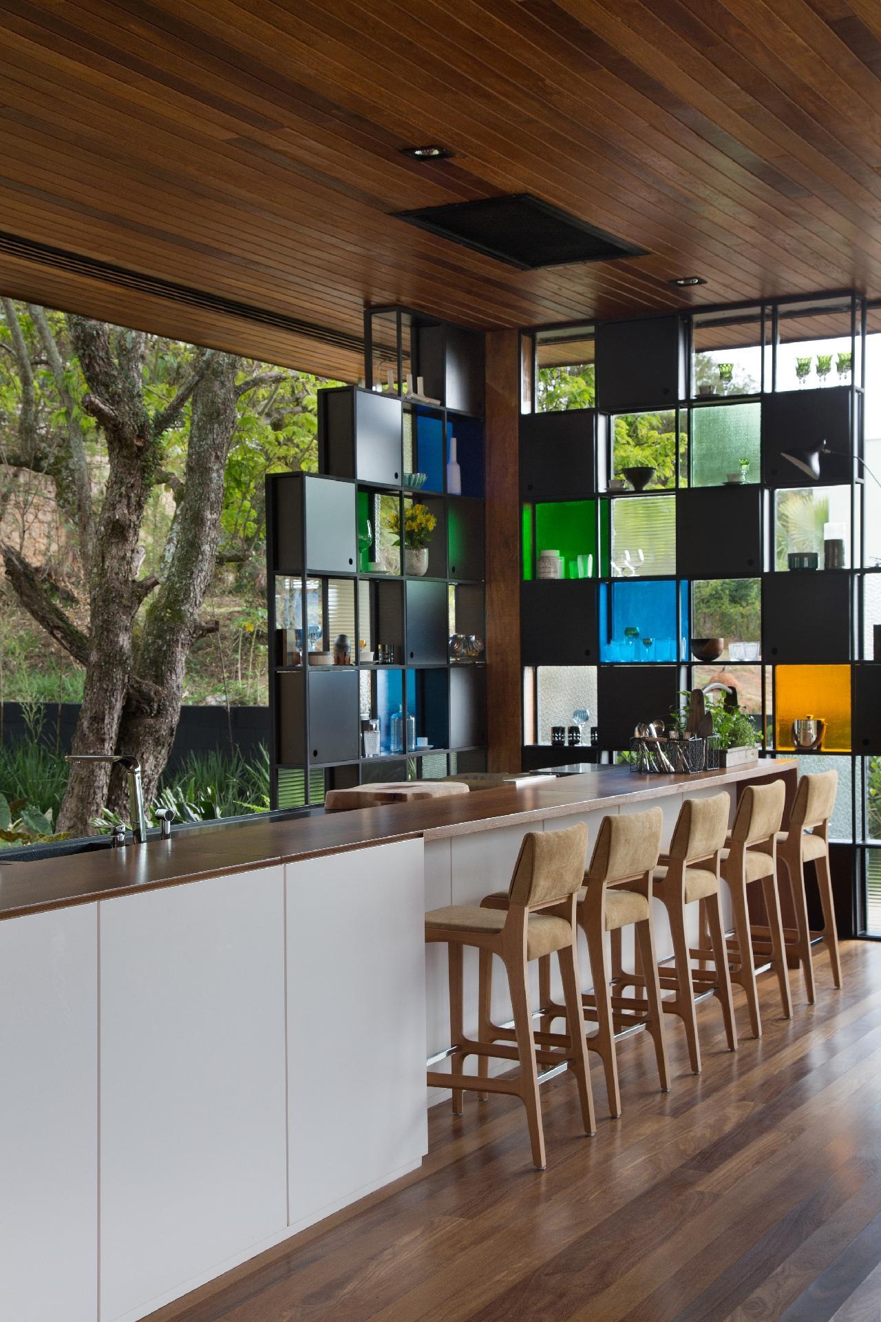 Os nichos em aço preto e vidro colorido formam a estante-bar da área gourmet, desta casa de campo em Campinas (SP). As banquetas Anna, criadas por Jader Almeida, compõem a bancada. O arquiteto Otto Felix assina o projeto de arquitetura e interiores