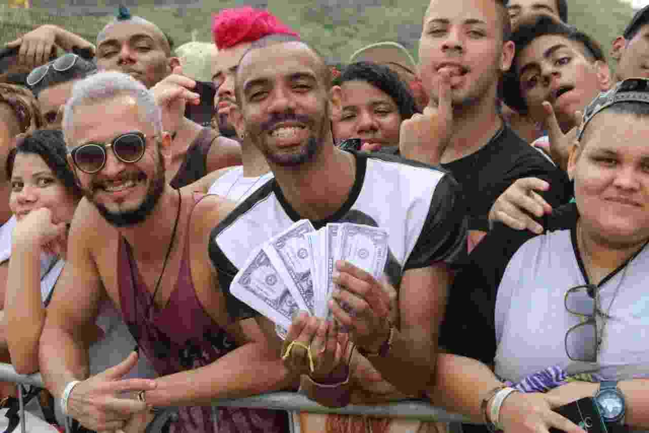 """26.set.2015 - José Dionísio Junior na fila para o sexto dia de Rock in Rio 2015. Os fãs trouxeram notas falsas de dólares, com o rosto de Rihanna, para uma performance na música """"Bitch Better Haver My Money"""". - Zulmair Rocha/UOL"""