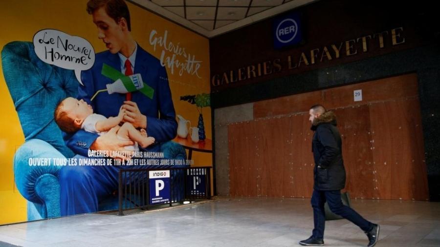 """Anúncio intitulado """"O novo homem"""", nas Galerias Lafayette, mostra homem engravatado dando mamadeira a um bebê. Paris, 8 de dezembro de 2018 - REUTERS/Stephane Mahe"""