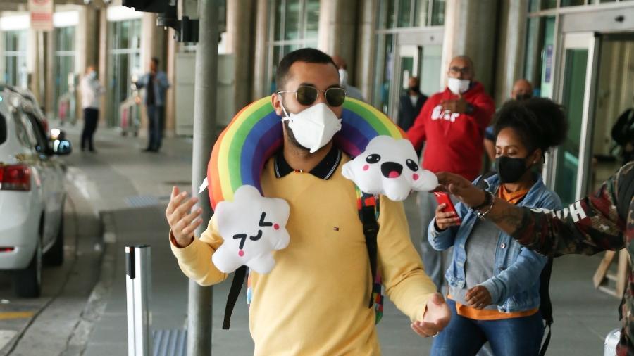 Gil do Vigor desembarca no aeroporto de Congonhas, em São Paulo, com travesseiro de viagem de arco-íris - Lucas Ramos/AgNews