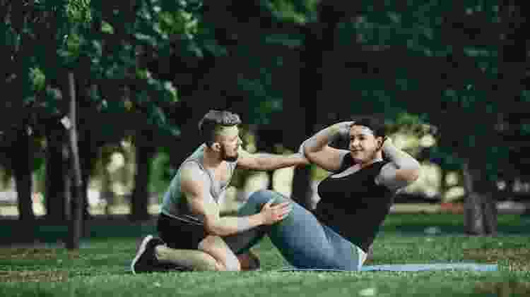 profissional de educação física, treinador orientando aluno, personal, exercício para emagrecer - iStock - iStock