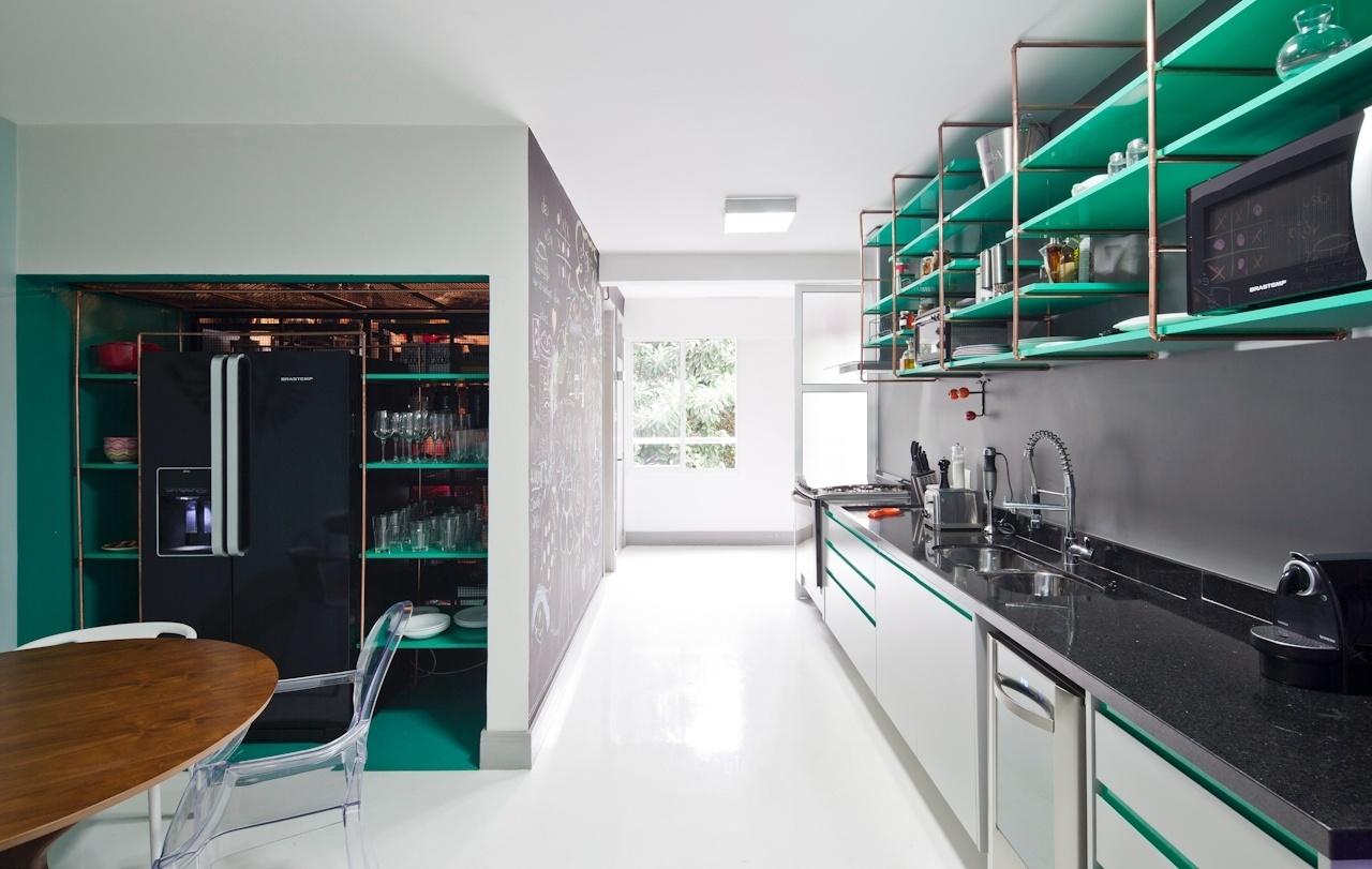 A cozinha é muito bem iluminada e pela ausência de paredes e portas divisórias, acaba por integrar-se à ala social do apartamento Perdizes, em São Paulo. Desta forma, o ambiente aproveita, também, a luz natural que é refletida desde o living pelo piso resinado. Os interiores são assinados pelo SuperLimão Studio