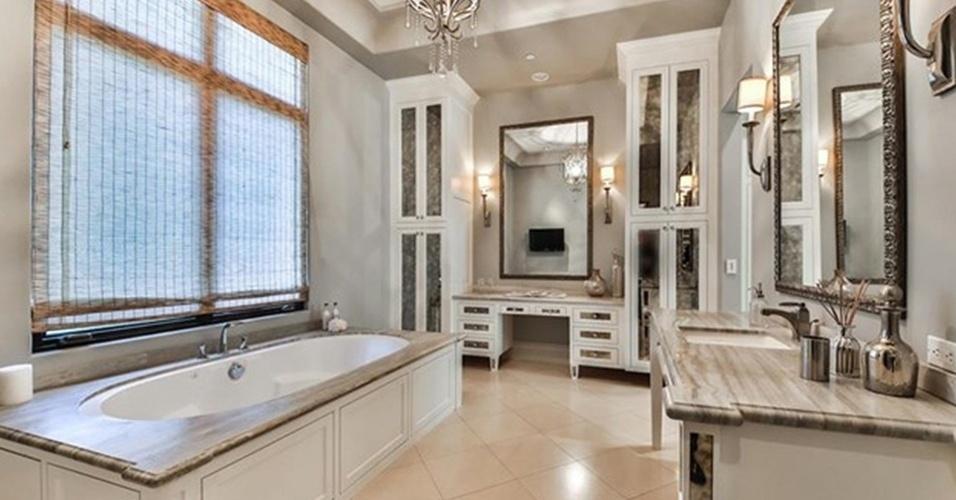 No banheiro da suíte, a banheira de hidromassagem é ladeada por mármore polido, que também estrutura os tampos da  penteadeira e da bancada com cuba embutida. A residência que pertence à cantora Britney Spears está à venda por R$ 32 milhões, na Califórnia, Estados Unidos