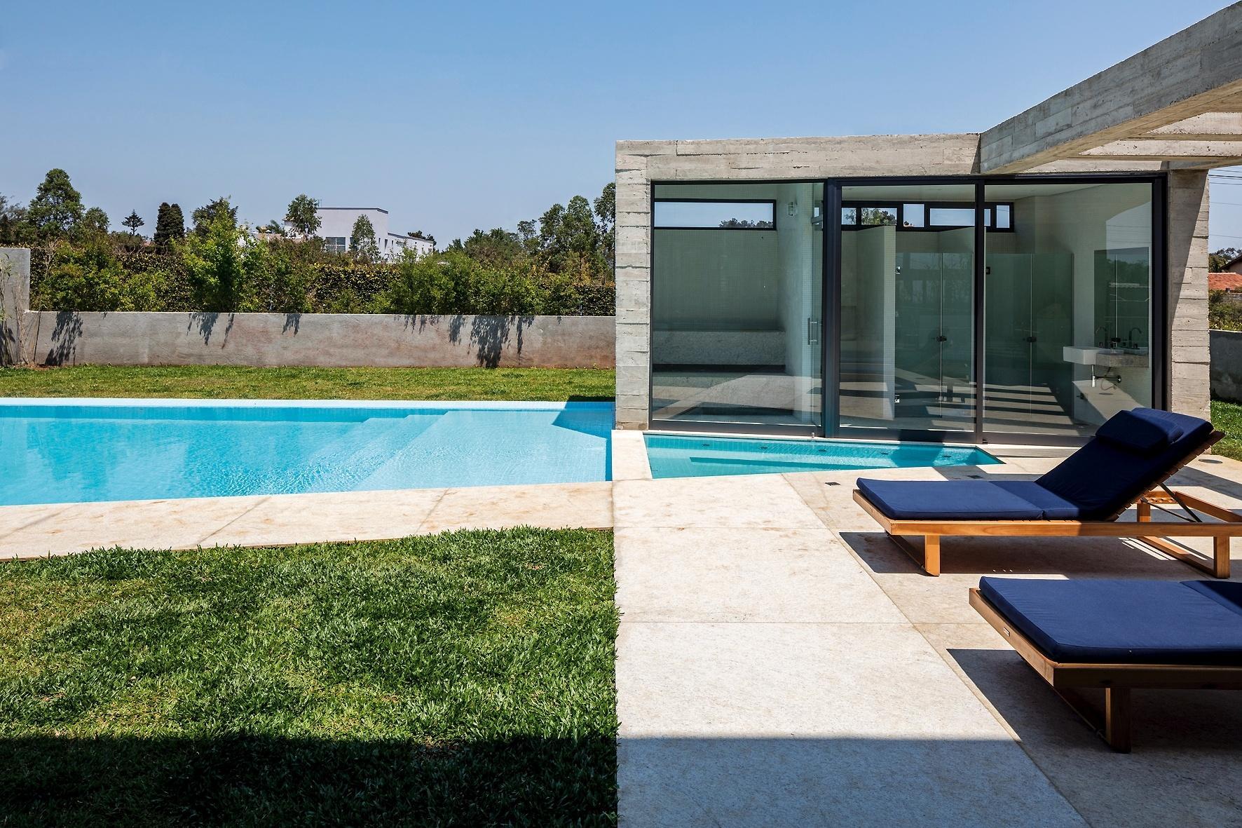Nos fundos da Casa Braga, projetada pelo arquiteto Gustavo Penna, a estrutura é pensada para o lazer: um pergolado de concreto (à dir.) liga a residência ao bloco da sauna (à dir.), todo envidraçado e voltado para as piscinas com profundidades distintas: uma é dedicada aos adultos (à esq.) e outras é ideal para as crianças