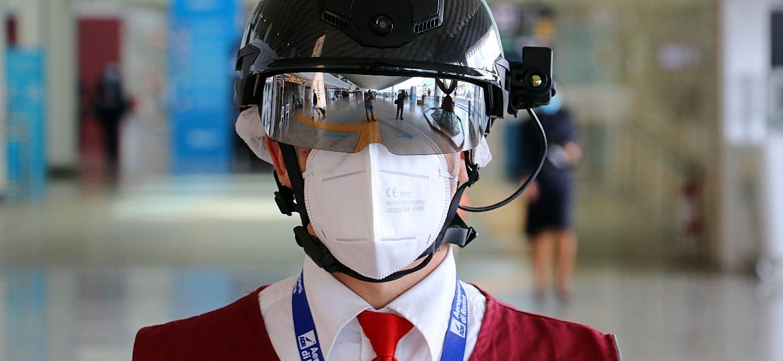 No aeroporto de Roma, funcionários utilizam um capacete que indica a temperatura dos passageiros - Divulgação