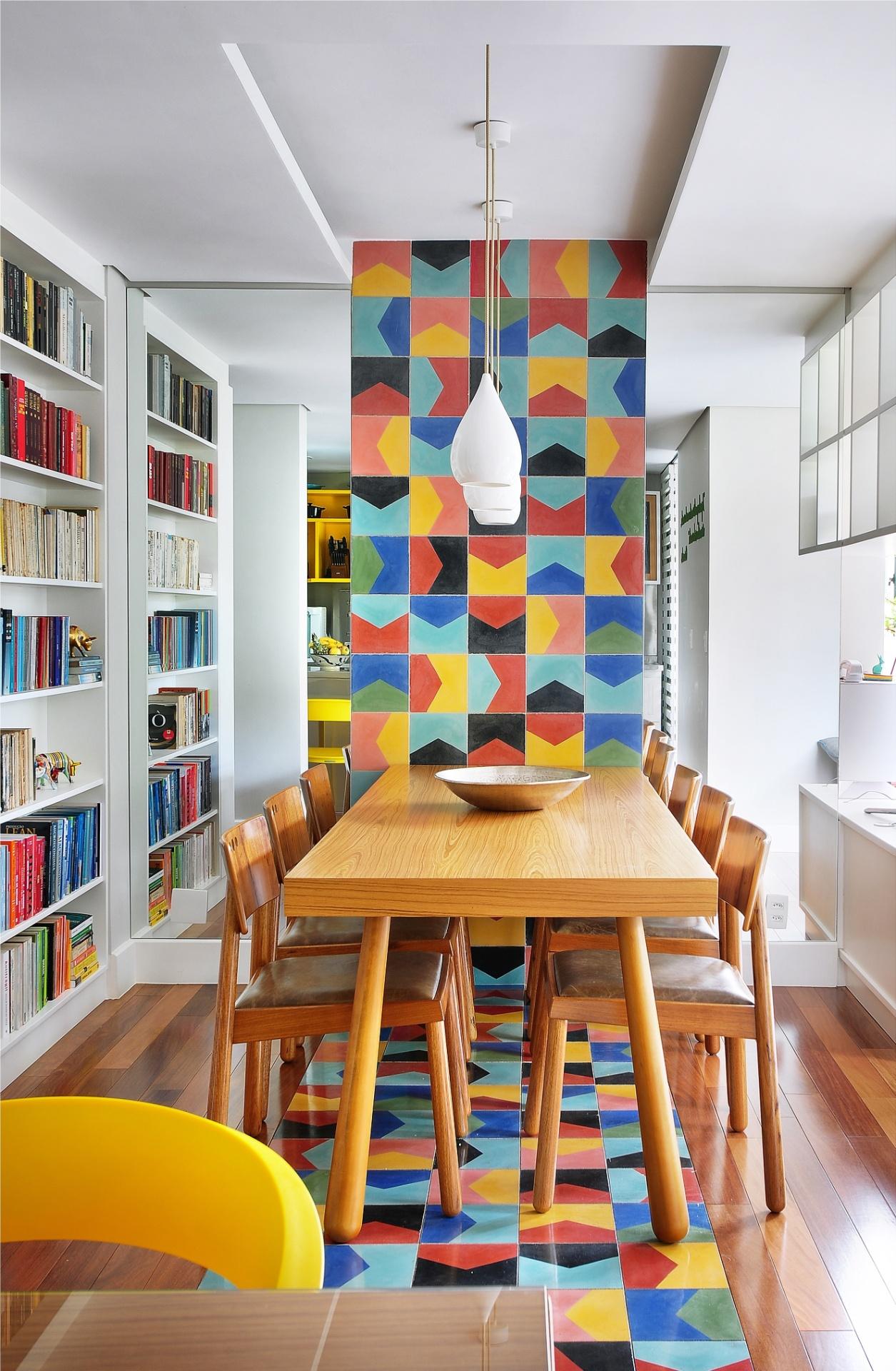 A sala de jantar do apê Jardim Marajoara integra-se à cozinha pelo caminho de ladrilhos coloridos que sobe até o teto. Na parede de fundo, espelhos dispostos nas laterais do painel de ladrilhos hidráulicos ampliam o espaço, enquanto a marcenaria composta de nichos vazados setoriza os ambientes sociais sem impedir a visão. As cadeiras em volta da mesa são assinadas por Sergio Rodrigues (Dpot) e têm assentos de couro. O design de interiores foi criado por Ana Yoshida