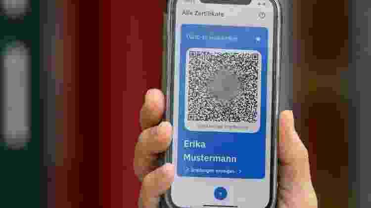 Homem apresenta um celular com o modelo de um passaporte digital de vacinação - Soeren Stache/AFP - Soeren Stache/AFP