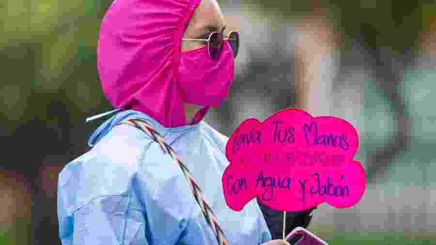 Mulher faz campanha pela prevenção contra o coronavírus em Bogotá, Colômbia - Getty Images