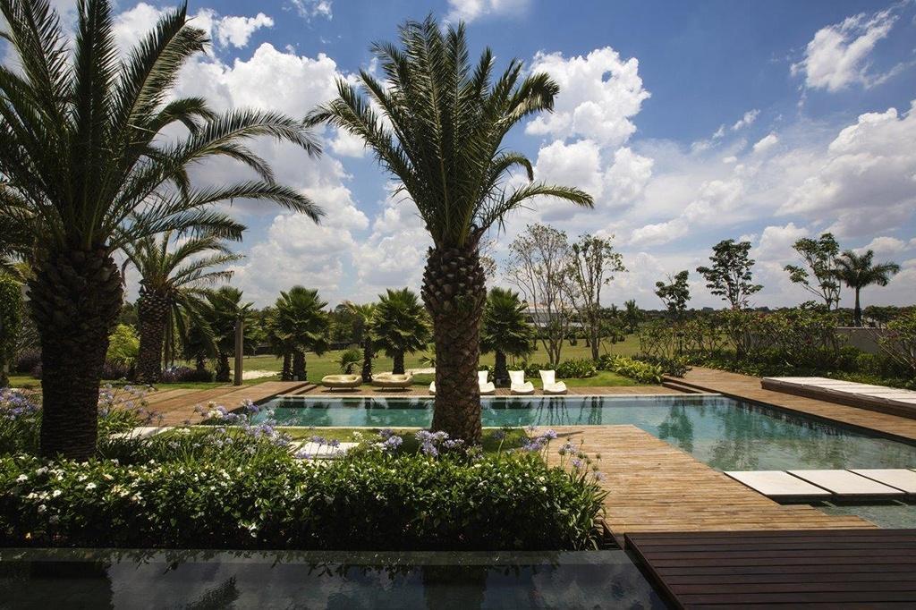 Rodeada por um deck de madeira e pelo paisagismo com espécies tropicais, a piscina em forma de L é um dos pontos altos dessa casa de campo no interior paulista. O projeto é do arquiteto Léo Shehtman, que concebeu os espaços para um casal que admira design contemporâneo