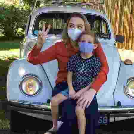 Arthur no colo da mãe em frente ao carro que levou comida a quem precisa - Arquivo pessoal - Arquivo pessoal