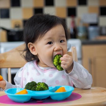Criança asiática comendo brocólis - Istock