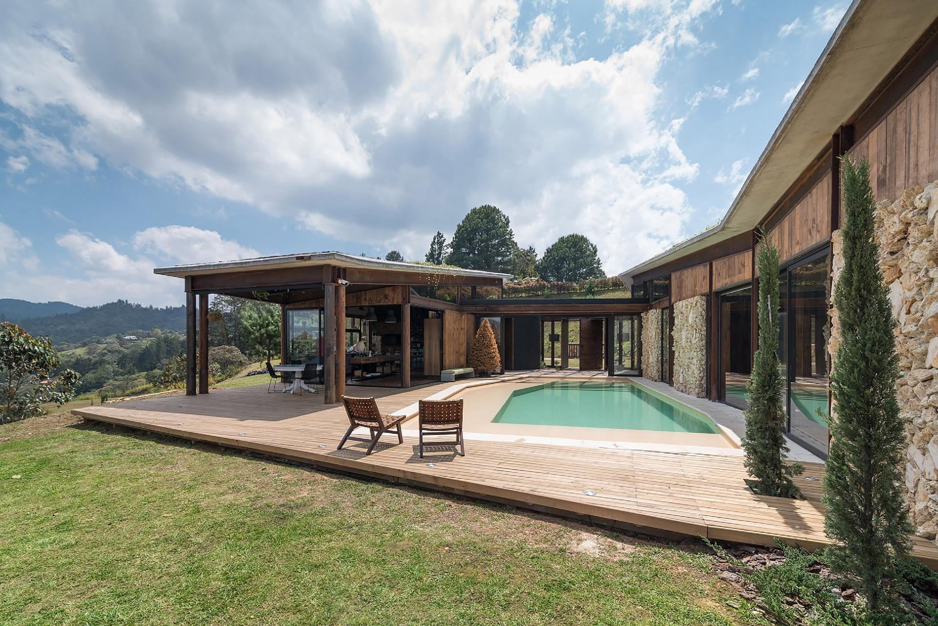 A casa Gozu, do coletivo colombiano de arquitetos OPUS, fica em um condomínio de El Retiro, Antioquia, região montanhosa da Colômbia. A construção está a 2.220 m de altura e o entorno de bosques confirma a posição privilegiada quanto à vista, incidência de ventos e natureza exuberante