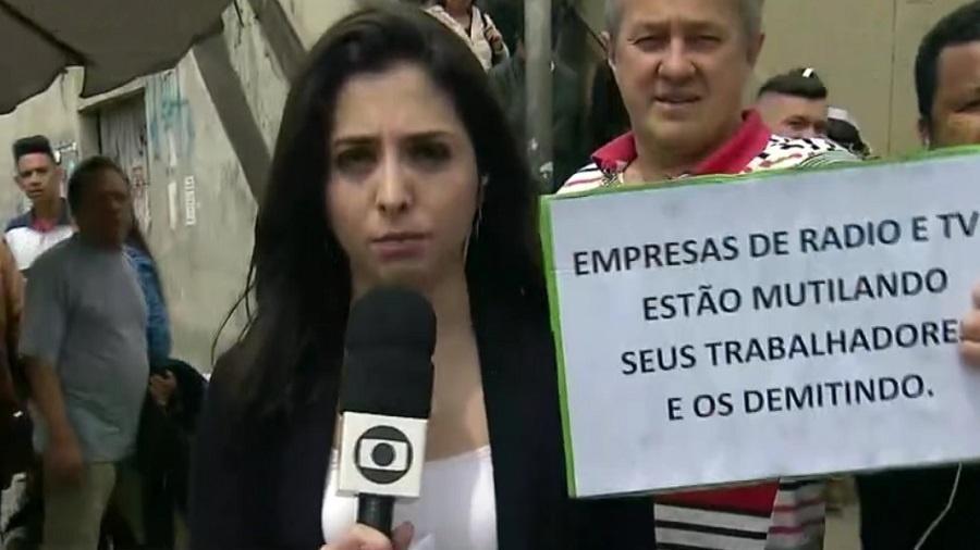 """Homens protestam durante transmissão ao vivo do """"SP1"""" com a repórter Cinthia Toledo - Reprodução/TV Globo"""