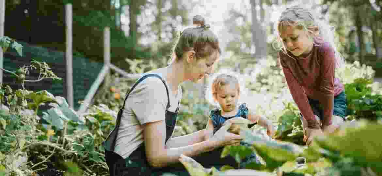 Mãe e a filhas cultivam horta: incentivo ao contato com a natureza - Getty Images